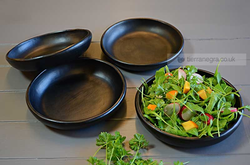 Four black ceramic serving plates